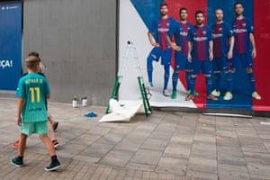 Boy wearing a Barcelona shirt walks past Camp Nou stadium