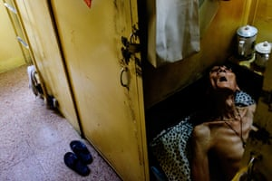 A resident in his coffin apartment. Hong Kong's coffin homes have a reputation for sheltering convicted criminals, retirees, drug abusers and the mentally ill. This photo was taken in a coffin apartment called Lucky House in Hong Kong in June 2017. By Benjamin Haas for The Guardian.