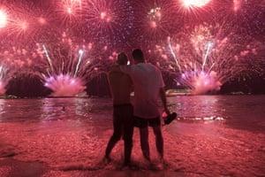 Two men watch the fireworks in Rio de Janeiro, Brazil.