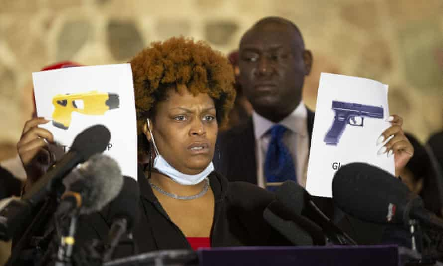 Daunte Wright's aunt Nyesha Wright holds up two printed images depicting a Taser and a gun while discussing her nephew's death.