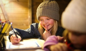 A young girl fills in an activity workbook on a day trip to Walby Farm, Cumbria