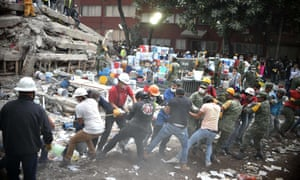 Rescuers, firefighters, policemen, soldiers and volunteers search for survivors in a flattened building in Mexico City. The mayor said across the city 52 people had been pulled out alive.