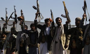 Pro-Houthi tribesmen hold weapons aloft during a tribal gathering in Sana''a, Yemen, in December.
