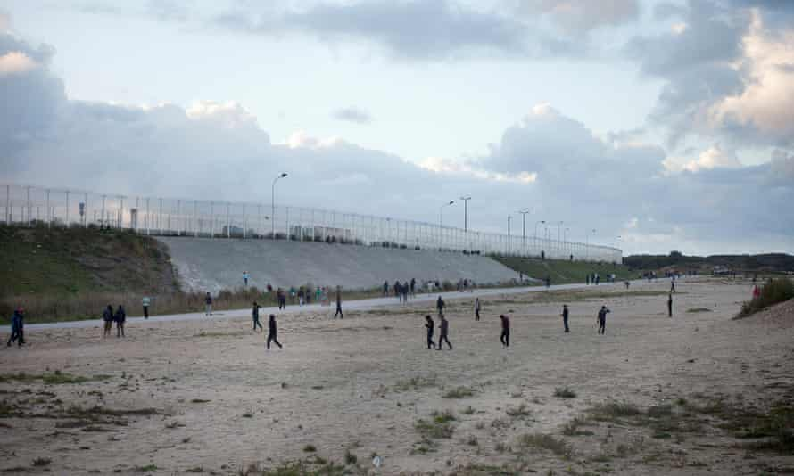 Boys and young men play cricket by the fence that surrounds the Calais camp