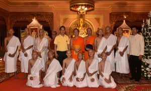 The rescued boys together with their coach wearing white robes pose with Buddhist monks.