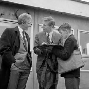 Scottish footballers Billy McNeill (centre) and Denis Law sign autographs for a young fan after their arrival at Heathrow Airport in April 1965 for Scotland's game against England.