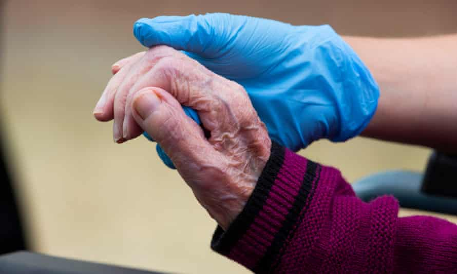 A care holds a resident's hand
