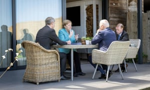 Biden and Merkel during a meeting with their advisers at an outdoor table.