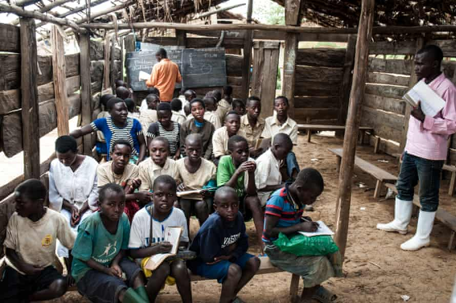 Two groups of children share a roofless classroom as teachers conduct separate lessons