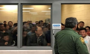 Men are crowded in a room at a Border Patrol station in McAllen, Texas