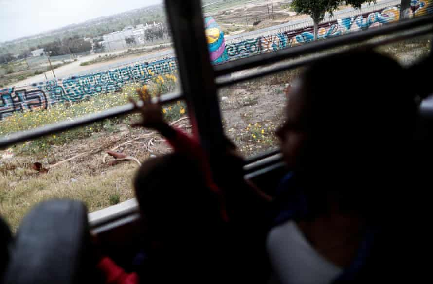 A bus rides past the border fence between Mexico and the US in Tijuana, 29 April