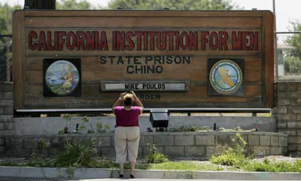 In this 2009 file photo, a woman takes a photograph at the entrance of the California Institution For Men State Prison Chino, California