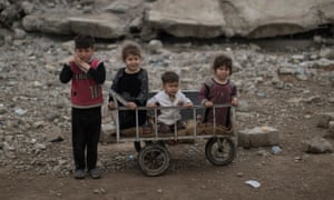 Children wait as their mother collects food being distributed in a neighbourhood recently retaken by Iraqi security forces