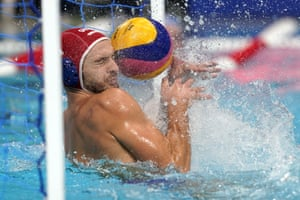 Greece's goalkeeper Emmanouil Zerdevas gets hit by a shot that bounced off him for a goal during their 6-6 draw with Italy in the preliminary round of the water polo