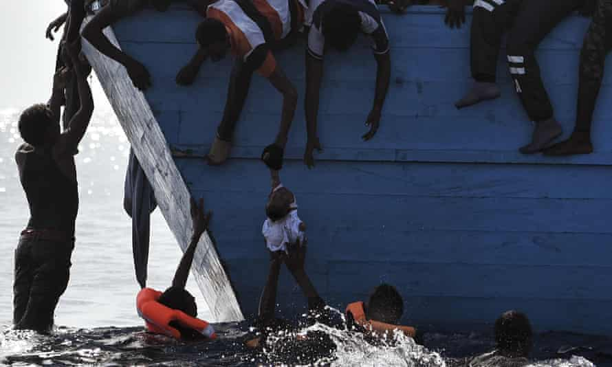 Migrants try to pull a child out of the water as they wait to be rescued 12 nautical miles north of Libya.