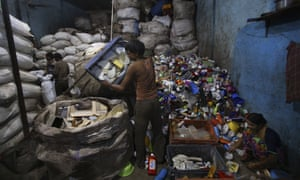 Workers sort through used plastic at a recycling unit in Mumbai, India