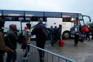 People carry their belongings as they board a bus at the start of their evacuation