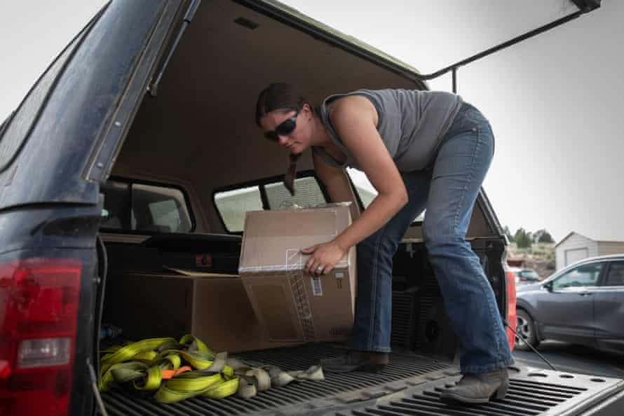 Valerie O'Dai unloads boxes from the back of a pickup truck.