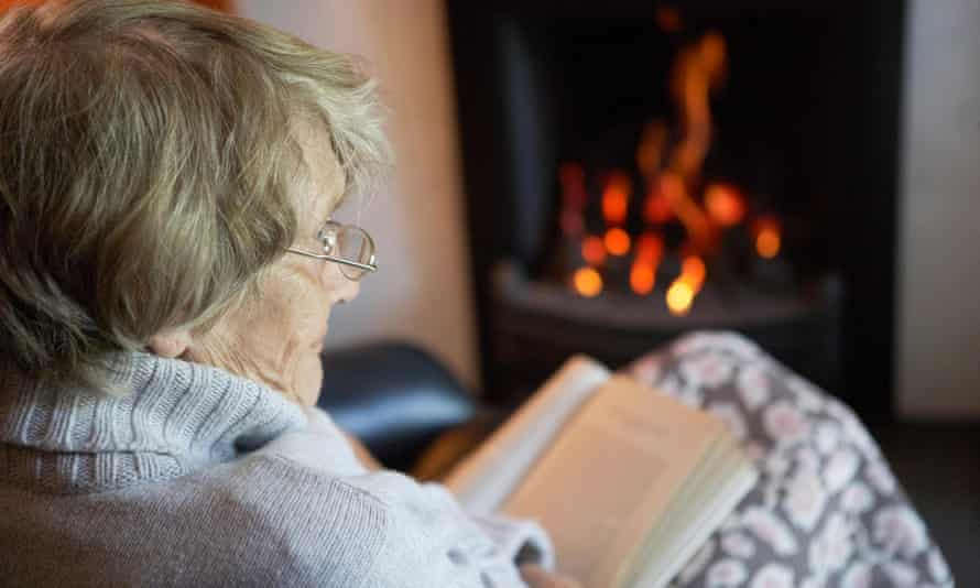 An older woman reading by a fire