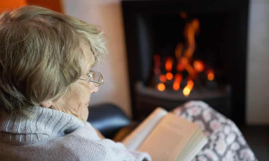 Older person reading by fire