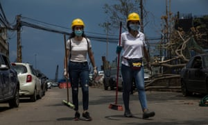 Two women carry brooms to help in the cleanup after last weeks explosion on August 13, 2020 in Beirut, Lebanon. The explosion, which killed more than 200 people and injured thousands more, is seen by many Lebanese as a deadly manifestation of government malpractice. (Photo by Daniel Carde/Getty Images)