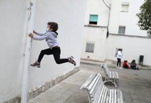 Kilian, six, wearing a face mask as he jumps from a bench in Igualada
