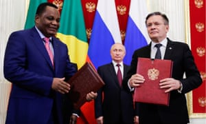 Vladimir Putin looks on as Rosatom CEO Alexey Likhachev and a Congolese official prepare to sign documents on Russian-Congolese talks at a ceremony in May.