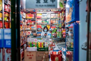 A vendor wears a protective mask as she waits for customers at a shop in Beijing.