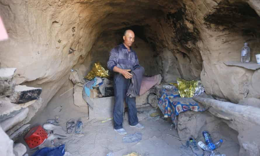 Shepherd Zhu Keming speaks to the media in a cave, where he saved the lives of six runners.