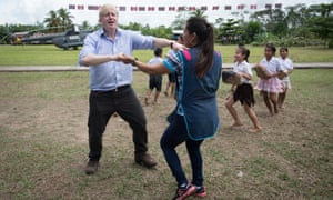 Boris Johnson dances with infant class teacher Adriana Pinedo during a visit to Peru.