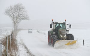 A tractor with a plough clears snow on the B3081 near to Shaftesbury, Dorset