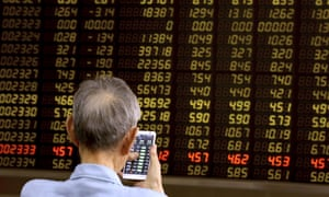 A man monitors stock prices at a brokerage in Beijing today