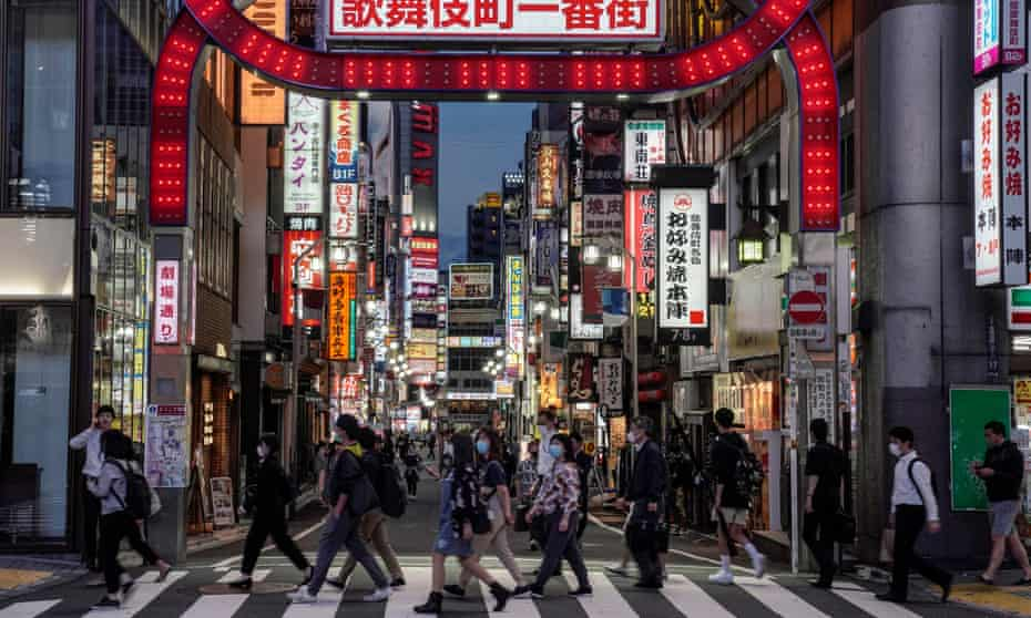 Commuters walk toward a railway station in front of an entrance to Kabukicho in Tokyo