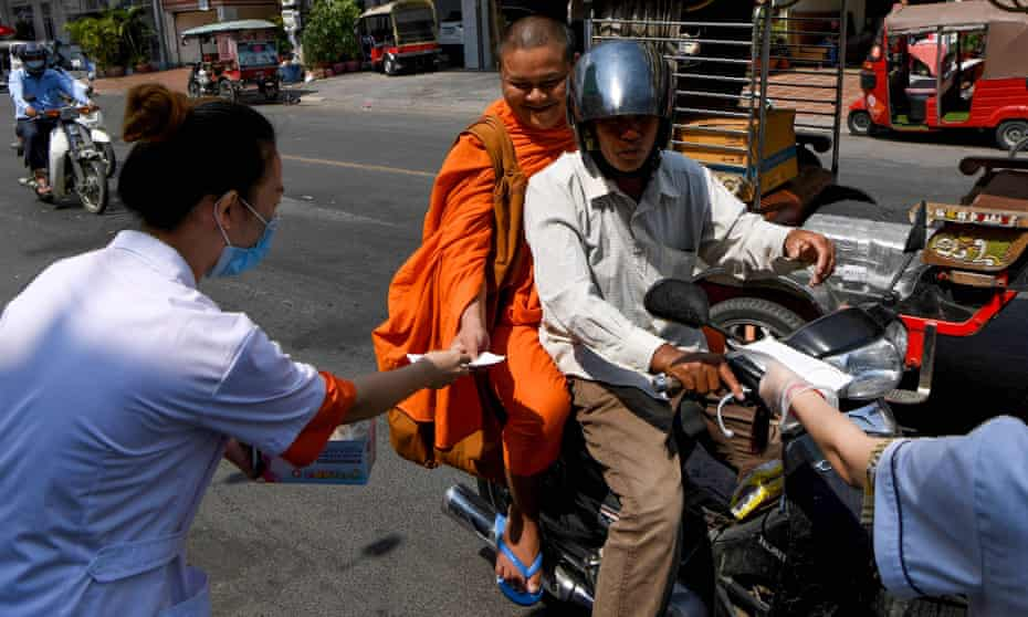 Volunteers hand out free face masks to people along a street in Phnom Penh, Cambodia in January.