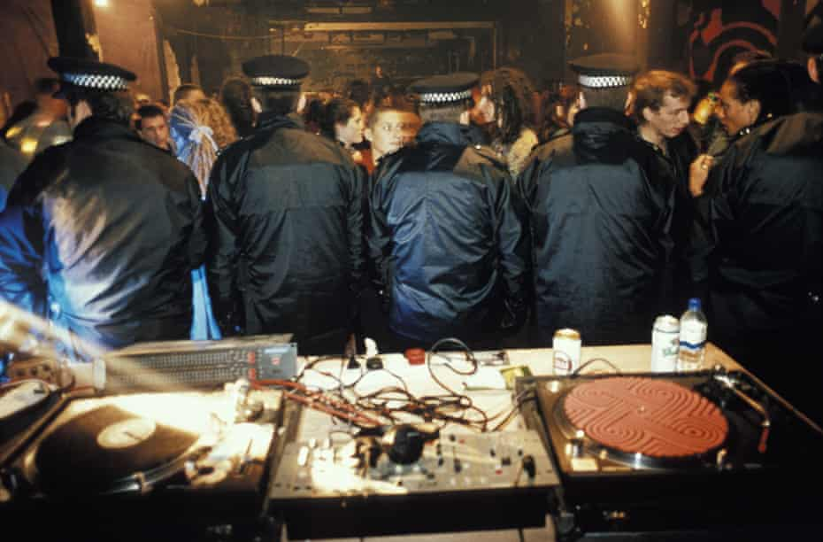 Police stand guard over the decks after busting an illegal warehouse party.