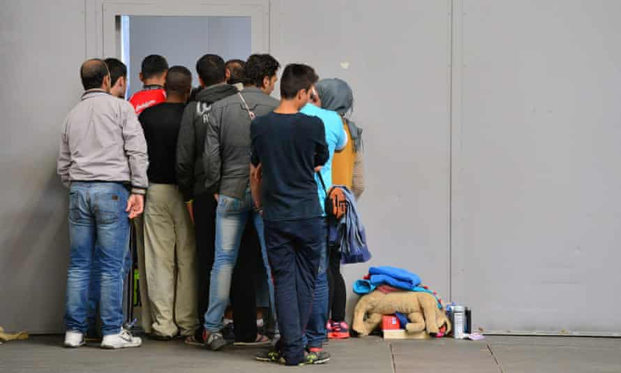 Refugees wait at the entrance to a clothing storage at an exhibition centre in Erfurt, Germany