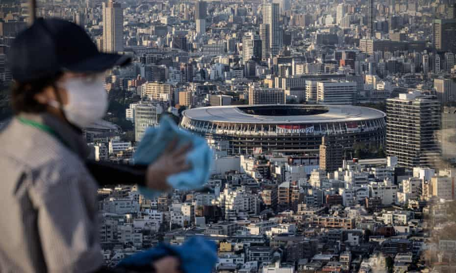 A cleaner wipes a window overlooking the Olympic Stadium on Shibuya Sky Deck in Tokyo.