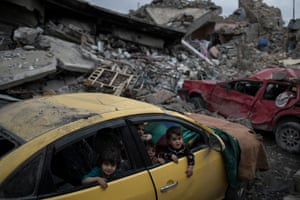 Children play inside a damaged car in a neighborhood recently retaken by Iraqi security forces.