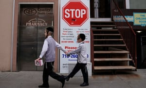 Children walk past a sign about a measles outbreak Brooklyn, New York, on 25 April.