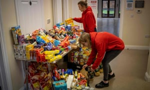 Staff organise food donations for vulnerable families at the Cooking Champions food bank in Grange Park, north London