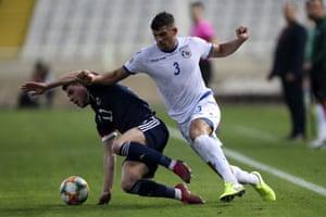 Cyprus' Nicholas Ioannou challenges Ryan Christie.