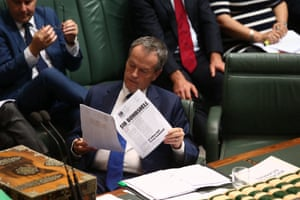 The opposition leader, Bill Shorten, reads about the Bell litigation and George Brandis for the convenience of photographers.