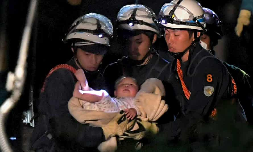 A baby is carried away by rescue workers in Mashiki town.