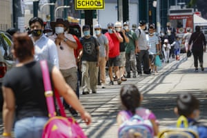 Pedestrians wearing protective masks wait on line for food donations during the Covid-19 pandemic, on Tuesday, 23 June , 2020, in the Corona neighborhood of the Queens borough of New York.