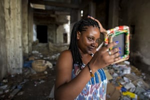 Desordes Woodline checks out her new braids after getting her hair done with a stylist in the quake-destroyed building in the Grand Rue market area.