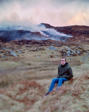 Uilleam, from the Isle of Barra, sitting on a hillside with fire in the distance