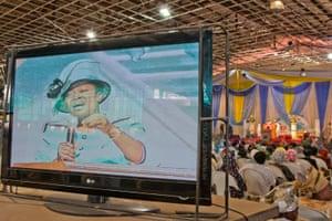 Prayer service shown on screen throughout an auditorium, Nigeria.