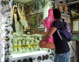 Touching La Flaquita (The Skinny Lady). Devotees travel for many days to reach what is considered the holiest shrine to Santa Muerte in the Tepito District of Mexico City.