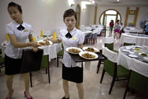 A North Korean waitress prepares to serve dinner to Chinese tourists at the Pegaebong hotel.