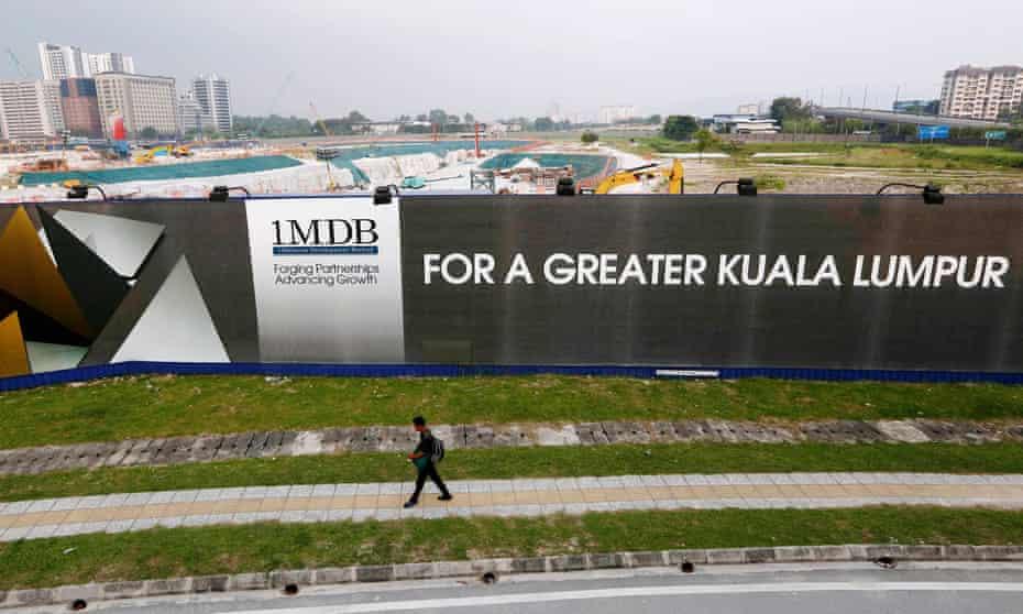 A man walks past a 1MDB billboard in Kuala Lumpur in 2015